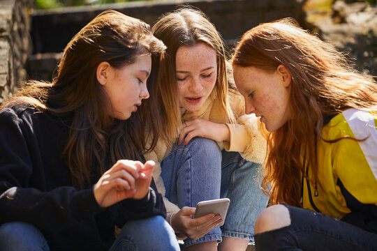 Three teenage girls sitting outdoors, checking their mobile phones.