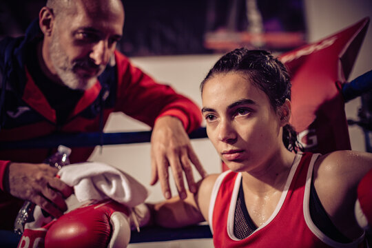 Portrait of boxing coach and female boxer sitting in boxing ring.