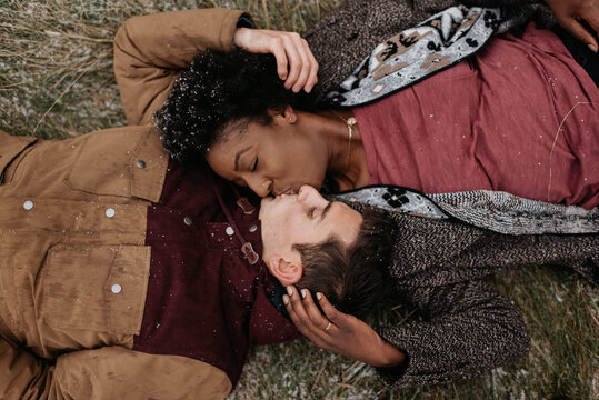 Overhead view of a black woman and white man on the ground, heads together, kissing.