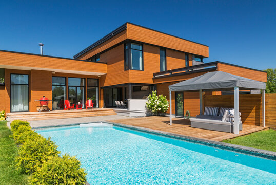 Exterior view of modern cube style home with stained horizontal wood cladding, swimming pool and wooden deck with gazebo canopy, Quebec, Canada.