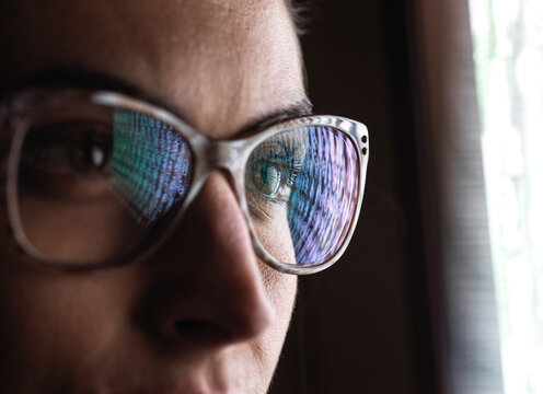 Female data analyst looking at data on screen, reflection in glasses.