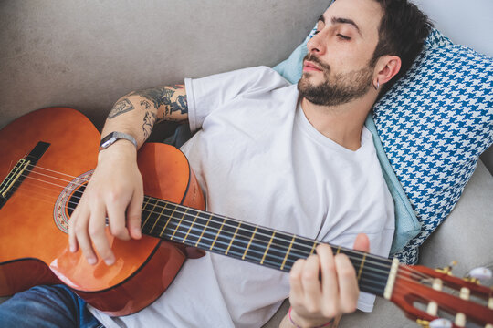 Young bearded man lying on sofa, playing acoustic guitar.