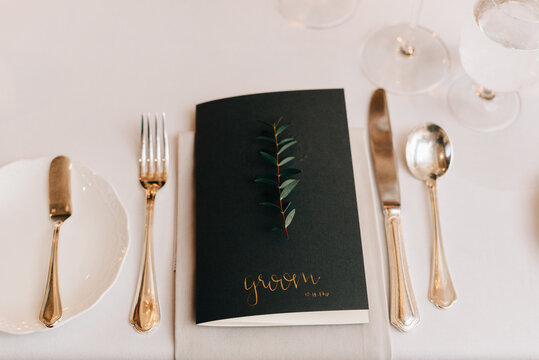High angle close up of place setting at a wedding table, with black name card and silver cutlery.