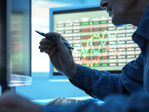 Close up of stock market trader analysing share price data on the screen.