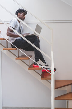 Young man with short dreadlocks sitting on staircase, typing on laptop.