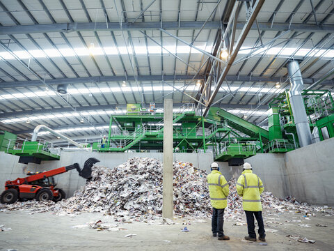 Workers inspecting waste paper in waste recycling plant.