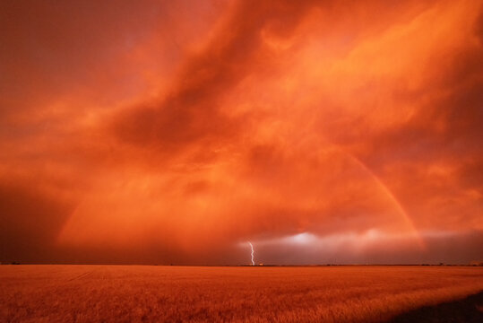 A dust storm with vivid orange sky and rainbow, and cloud-to-ground lightning strike.