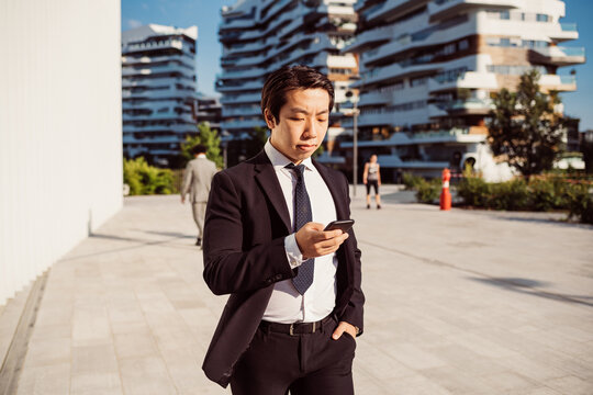 Portrait of Asian businessman wearing dark suit, checking mobile phone.
