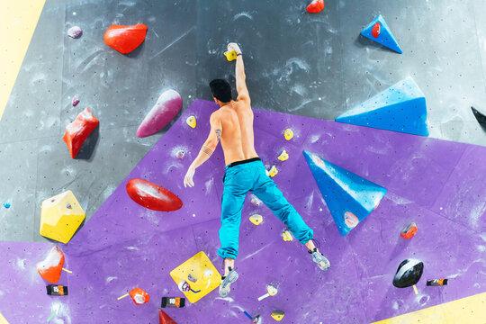Rear view of man ascending rock climbing wall.