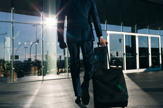 Businessman with wheeled luggage passing glass building, Malpensa, Milan