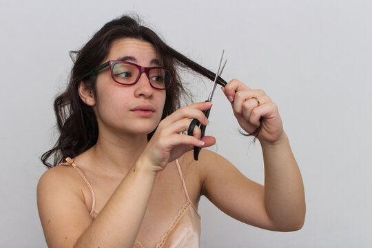 photo taken on white background in studio woman cutting her own hair