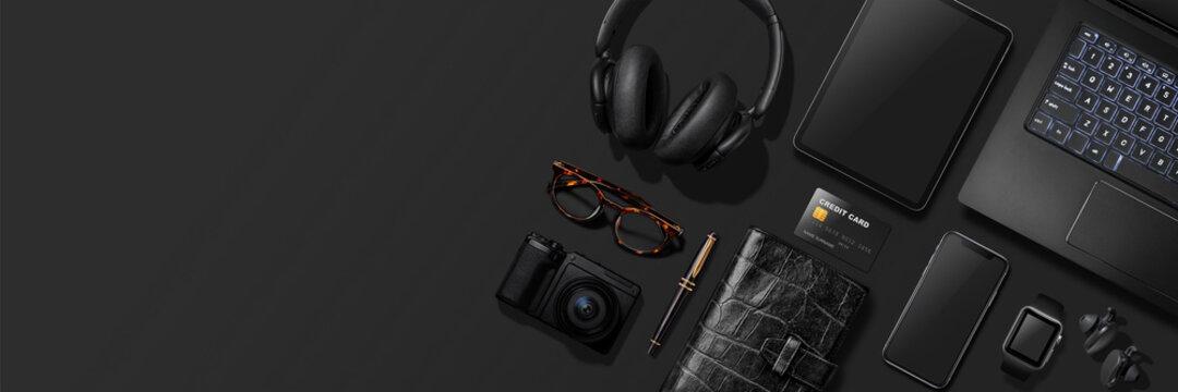 黒いテーブルの上にある、ノートパソコン、スマートフォン、タブレット、スマートウォッチ、カメラ等黒いアイテム。真上からのアングル。