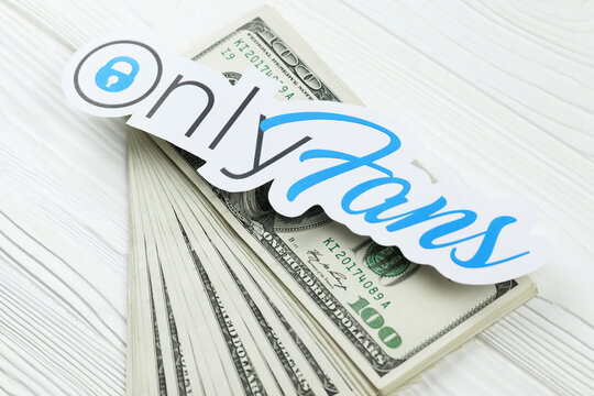 KHARKOV, UKRAINE - FEBRUARY 14, 2021: Onlyfans paper logo with dollar bills on white wooden table. OnlyFans is content subscription service based in London