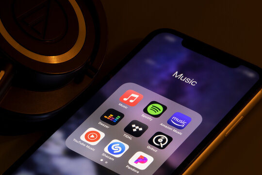Portland, OR, USA - Mar 16, 2021: Assorted music apps - Apple Music, Spotify, Amazon Music, Deezer, TIDAL, Qobuz, YouTube Music, Shazam, and Pandora - are seen on an iPhone next to headphones.