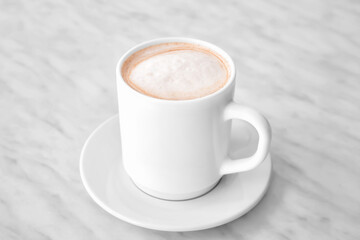 Cup of tasty latte on light background
