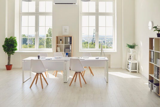 Interior of cozy light office room with big table, modern chairs and large windows