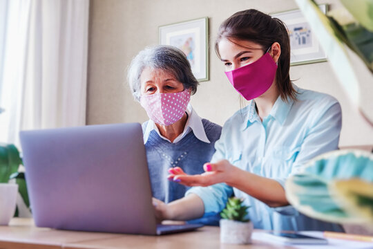 A positive adult daughter, together with an elderly gray-haired mother, sits on the couch and searches for useful information and content on the Internet using a laptop - Face masks as protection