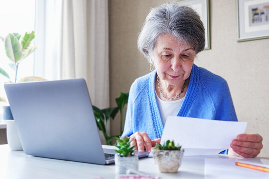 Elderly woman reads a bank loan notice or letter - Grandmother works from home with laptop and paperwork - Planning budget and retirement benefits and managing finances