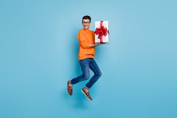 Full body portrait of cheerful handsome person jumping hold gift box toothy smile isolated on blue...