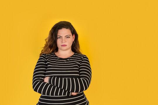 Mujer joven con cara de enfado y brazos cruzados sobre un fondo amarillo liso y aislado. Vista de frente. Copy space