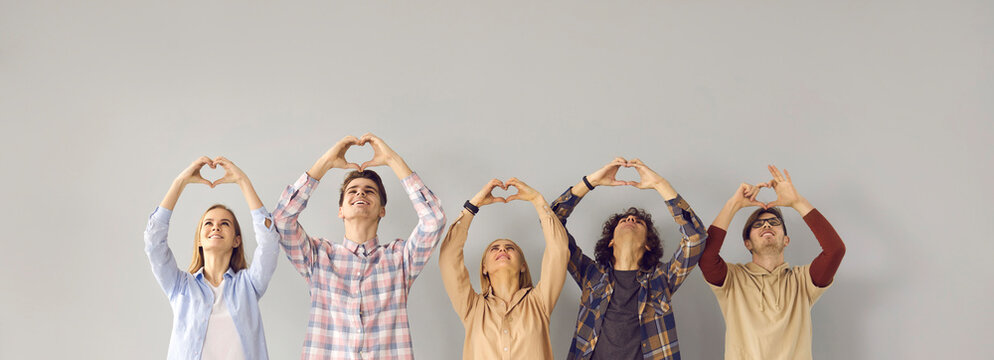 Group of happy grateful people looking up and doing symbolic heart shape hand sign gesture on gray background. Smiling young men and women promoting volunteering effort, sending love and thanking you