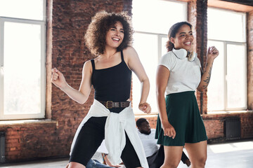 Happy young females during aerobics class in studio