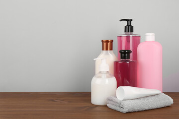 Wall Mural - Different shower gel bottles with towel on wooden table. Space for text