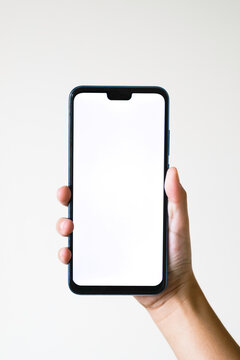 Business concept : Young man holding smartphone with blank screen on white background, closeup of hand, advertising text selling marketing products, mock up, Space for text.