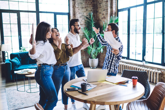 Happy multiracial coworkers cheering each other around table