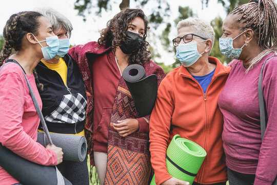 Multiracial women having fun at park outdoor while wearing safety face masks for coronavirus outbreak - Multi generation people after yoga class