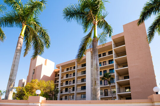 Florida gulf of mexico coast with luxury expensive apartment condominium condo building with palm trees in sunny summer