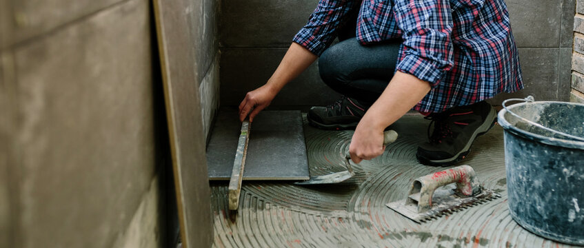 Female bricklayer checking the floor with a level to install a tile floor