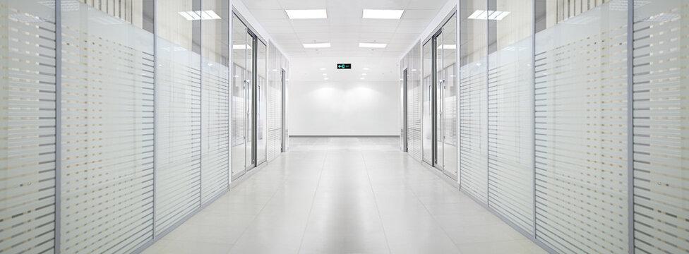 Empty bank office corridor with glass walls and doors