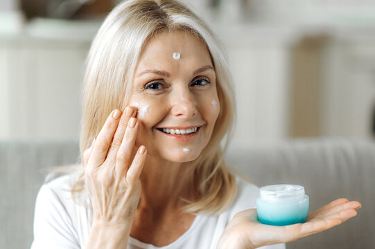 Portrait of a caucasian middle aged blonde woman. Beautiful happy woman holds a vessel with a face care cream, applies a moisturizer or anti-aging cream to the face, skin care concept, sitting on sofa