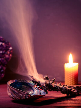 Smudging sage with dense smoke. Copy space. Amethyst crystal and burning bees wax candle at background. Smudging sage, amethyst and beeswax candles can be used to cleanse your home of negative energy.