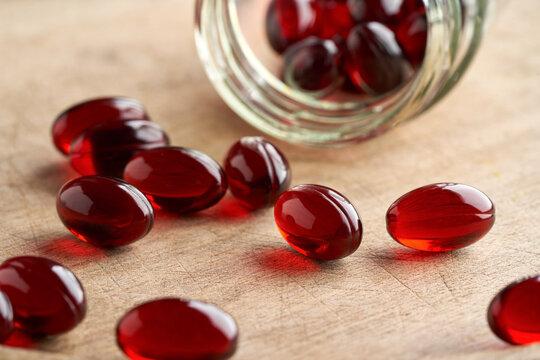 Krill oil pills spilled from a glass jar
