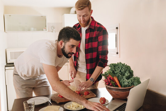 Young Male Couple Learning Cooking Online