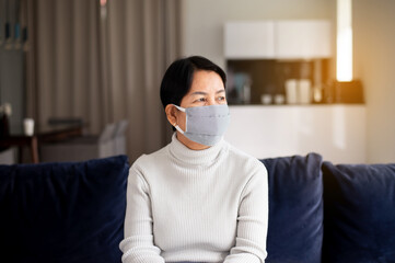 Elderly woman wearing face masks protect corona virus or covid-19 during spreading at home,Social...