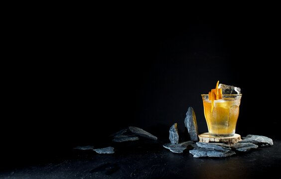 Old fashioned whiskey cocktail, orange garnish against a dark moody black background with candle