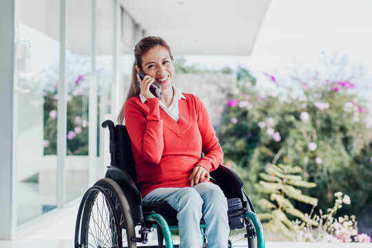 mexican woman talking by phone in wheelchair at workplace in Mexico city