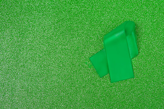 World mental health day. Green ribbon on green glittering background. Copy space for text, mock up.