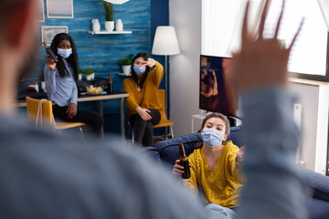 Man coming at party with friends wearing face mask preventing spread of coronavirus, women holding...