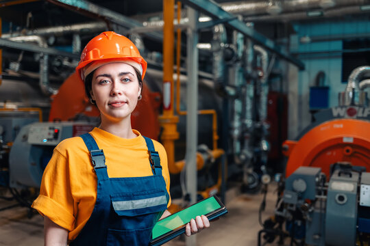 Industrial production concept. Portrait of a female engineer in uniform and helmet with a tablet in her hand. In the background-boiler equipment