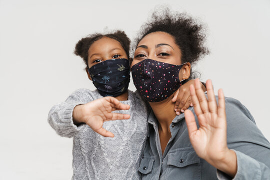 African mother and daughter in protective masks waving hands