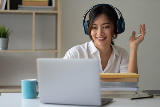Asian woman wearing headphones study online watching webinar podcast on laptop listening learning education course conference calling, elearning concept.