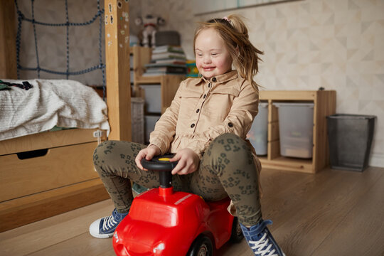 Full length portrait of happy girl with down syndrome riding toy car in cozyhome interior, copy space
