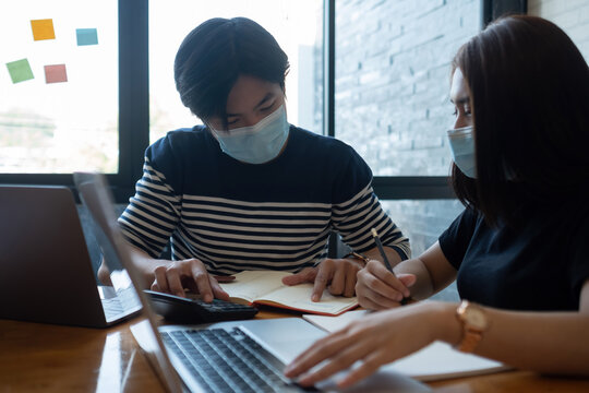 Asian woman and man workers meeting together with laptop for financial and wear protective masks prevent corona virus or covid19 at co working space .Health and teamwork concept.
