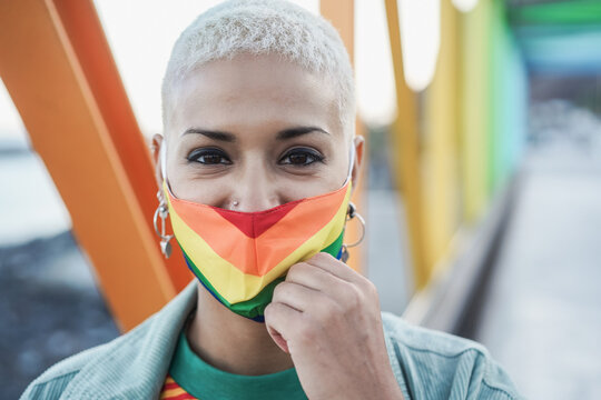 Young lesbian smiling on camera while wearing rainbow mask - Focus on face