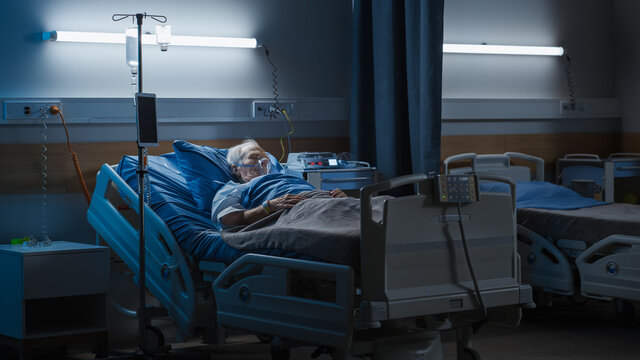 Hospital Ward: Portrait of Elderly Man Wearing Oxygen Mask Resting in Bed, Struggling to Recover after Covid-19, Sickness, Disease, Surgery. Old Man Fighting for His Life. Dark Blue Sad Shot