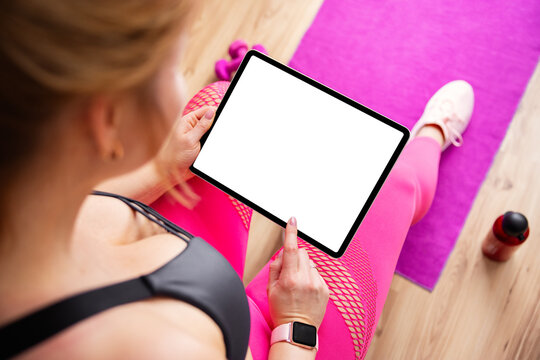 Woman holding tablet with blank screen during fitness training